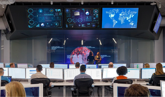 Security professionals working in front of large display monitors at the Microsoft Cyber Defense Operations Center