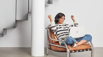 Person sitting cross-legged on a leather chair wearing headphones and looking at a laptop while smiling and holding their fists in the air.