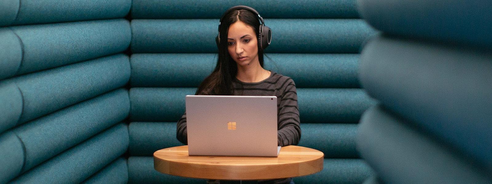 Uma mulher sentada sozinha usando fones de ouvido enquanto trabalha em seu computador com Windows 10.