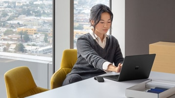 Contextual image of woman touching screen while working on Black Surface Laptop inside at conference room table