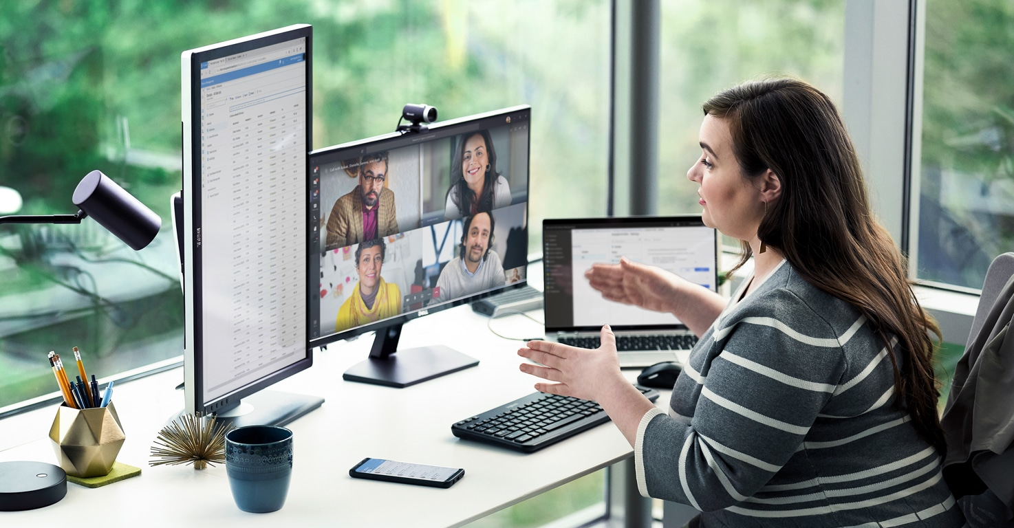Person participates in a video call with four other people visible on one monitor while looking at a document on another monitor and using Teams on a laptop.