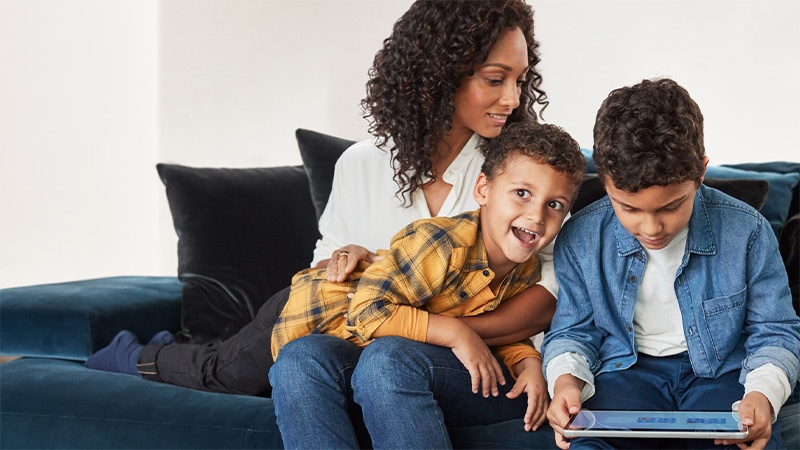 Mulher em um sofá com dois meninos jogando em um dispositivo Windows 10