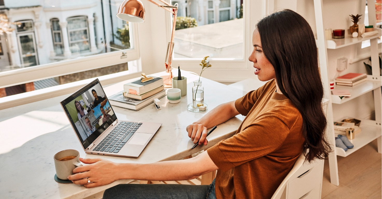Person seated at desk by a window engaged in a Teams video conference meeting displayed on a laptop.