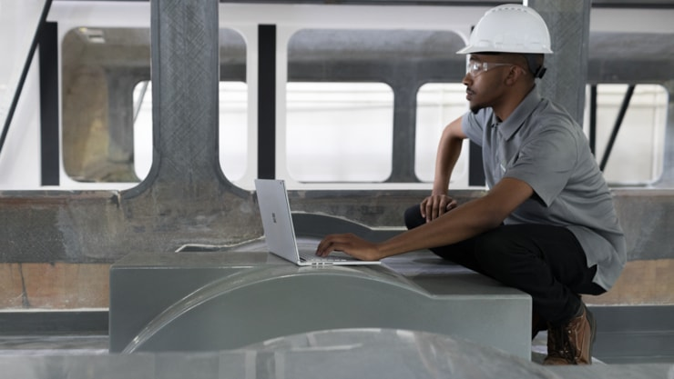 Person wearing a hard hat crouches down to use a laptop in a construction environment.