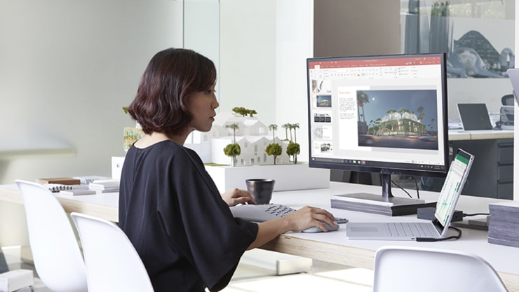 Person sits alone at a desk working on a PowerPoint presentation on a large desktop monitor.