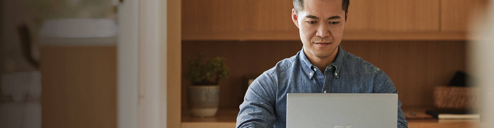 Person wearing a denim shirt sits alone looking at a laptop.