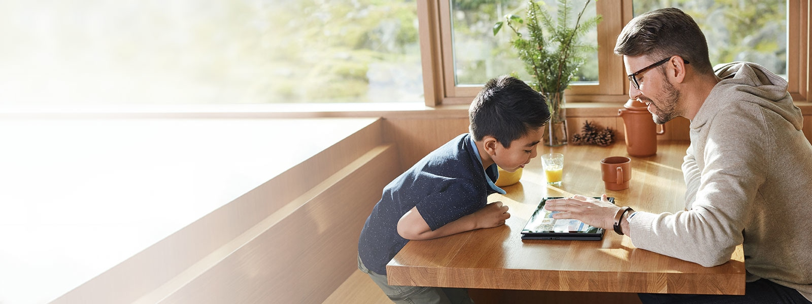 A father and son sit at the breakfast table across from each other looking at a Windows 10 PC