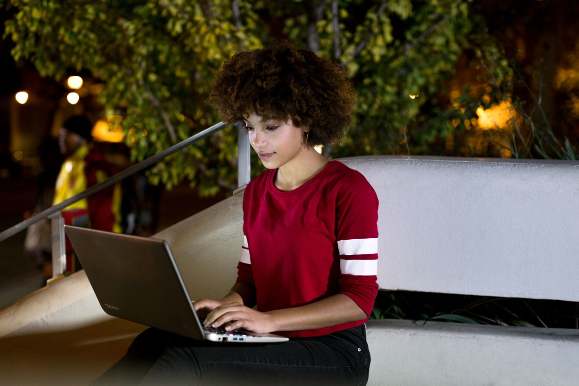 Person sitting outdoors at night using a laptop