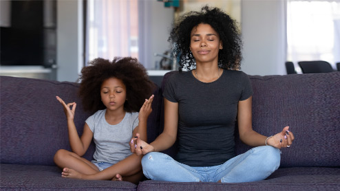 Photo credit: Photo credit: fizkes/iStock/Getty Images. Mother and young daughter doing yoga together at home on their couch.