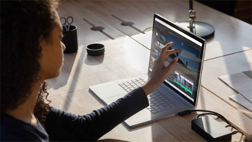 Woman touches a Windows 10 touch screen laptop
