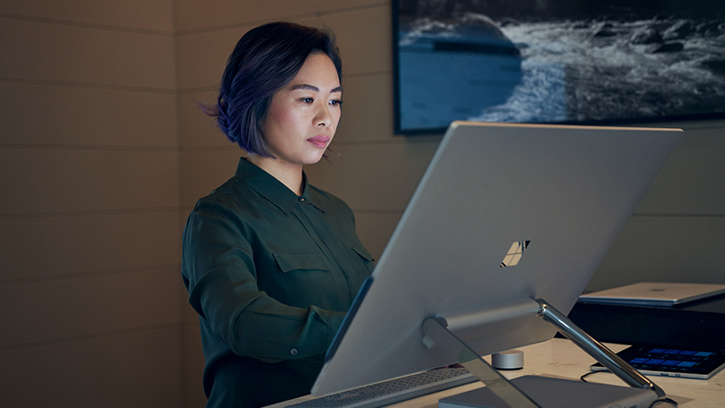 Side profile of a woman working on a Microsoft Surface Studio.