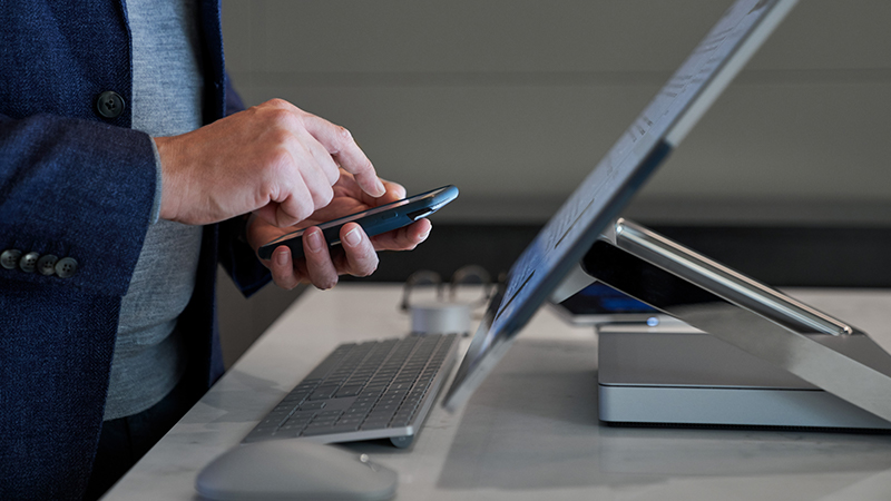 Side view close-up of a man typing on his phone while standing behind a Microsoft Surface Studio