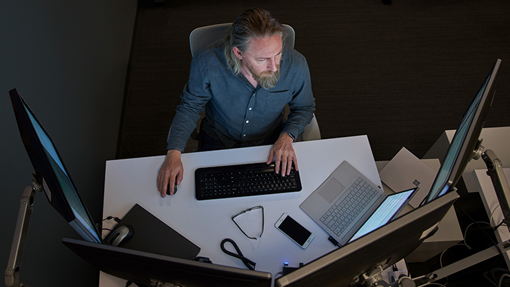 Top-down view of a man seated at a desk working on a Surface laptop connected to three large monitors.
