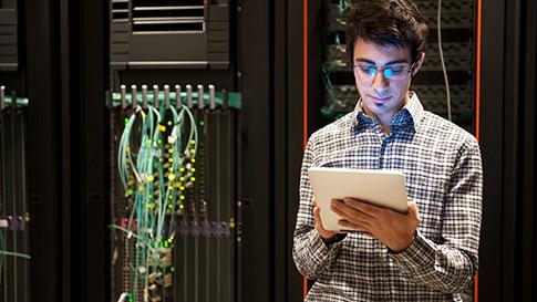 Um homem em uma sala de servidores usando um tablet para trabalhar.