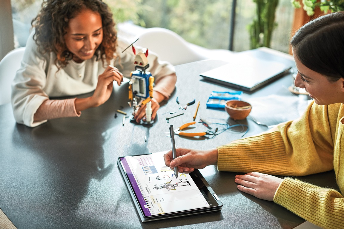 Two people sitting at a table designing and building a small robot. One person is using a pen and tablet device while the other person is holding the robot