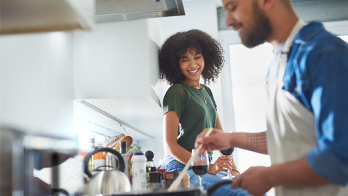 Photo credit: LaylaBird/E+/Getty Images. Smiling woman sitting on kitchen counter with a glass of wine watches man cook food on a stovetop.