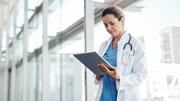 A doctor reading on a tablet