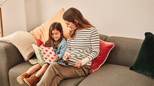 A young girl and her mother sitting on a couch reading a book