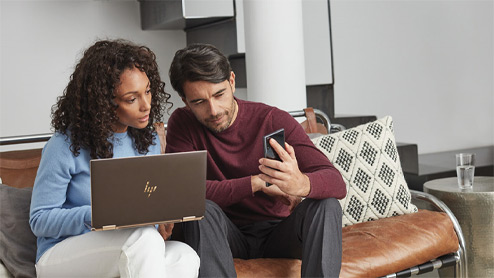 Man and woman sitting on a couch, looking at a mobile device and Windows 10 laptop
