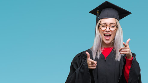 Photo credit: Aaron Amat/iStock/Getty Images. Young woman wearing graduation gown and pointing fingers and winking at camera.