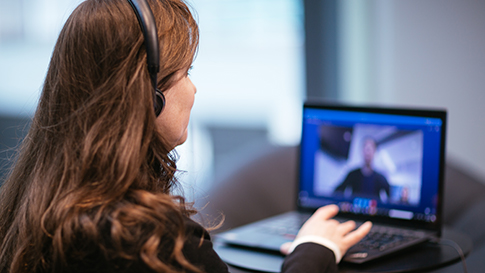 A woman wearing headphones and looking at a video conferencing screen on her laptop.