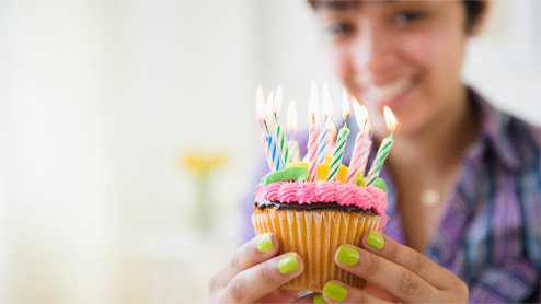 Photo credit: JGI/Jamie Grill/Getty Images. A smiling woman holding a cupcake with colorful birthday candles.