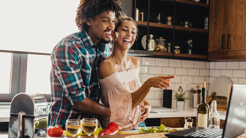 Photo credit: blackCAT/E+/Getty Images. Smiling man and woman look at recipe on Windows laptop while cooking together in kitchen