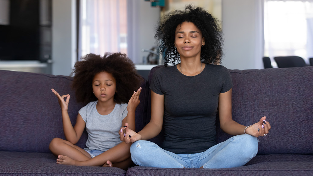 Photo credit: fizkes/iStock/Getty Images. Mother and young daughter doing yoga together at home on their couch.