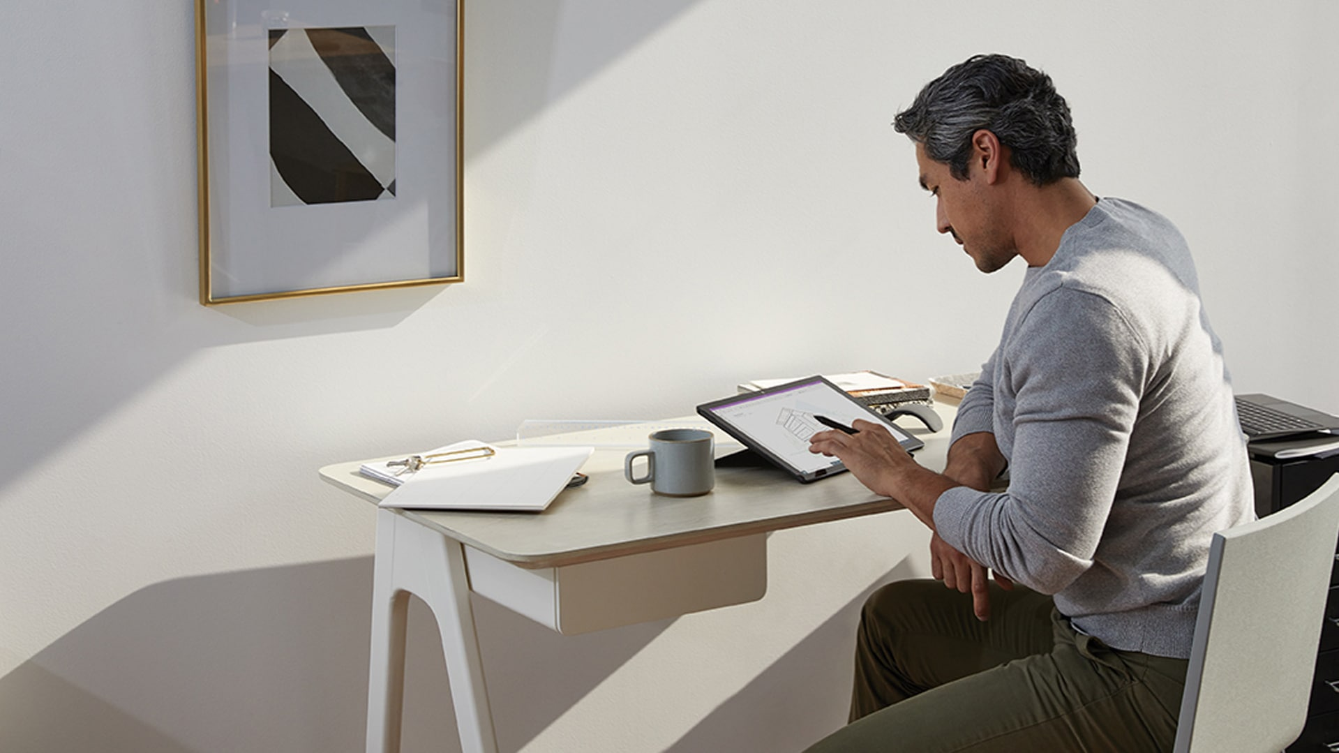 A man works from his home office with Surface Pen and Surface Pro