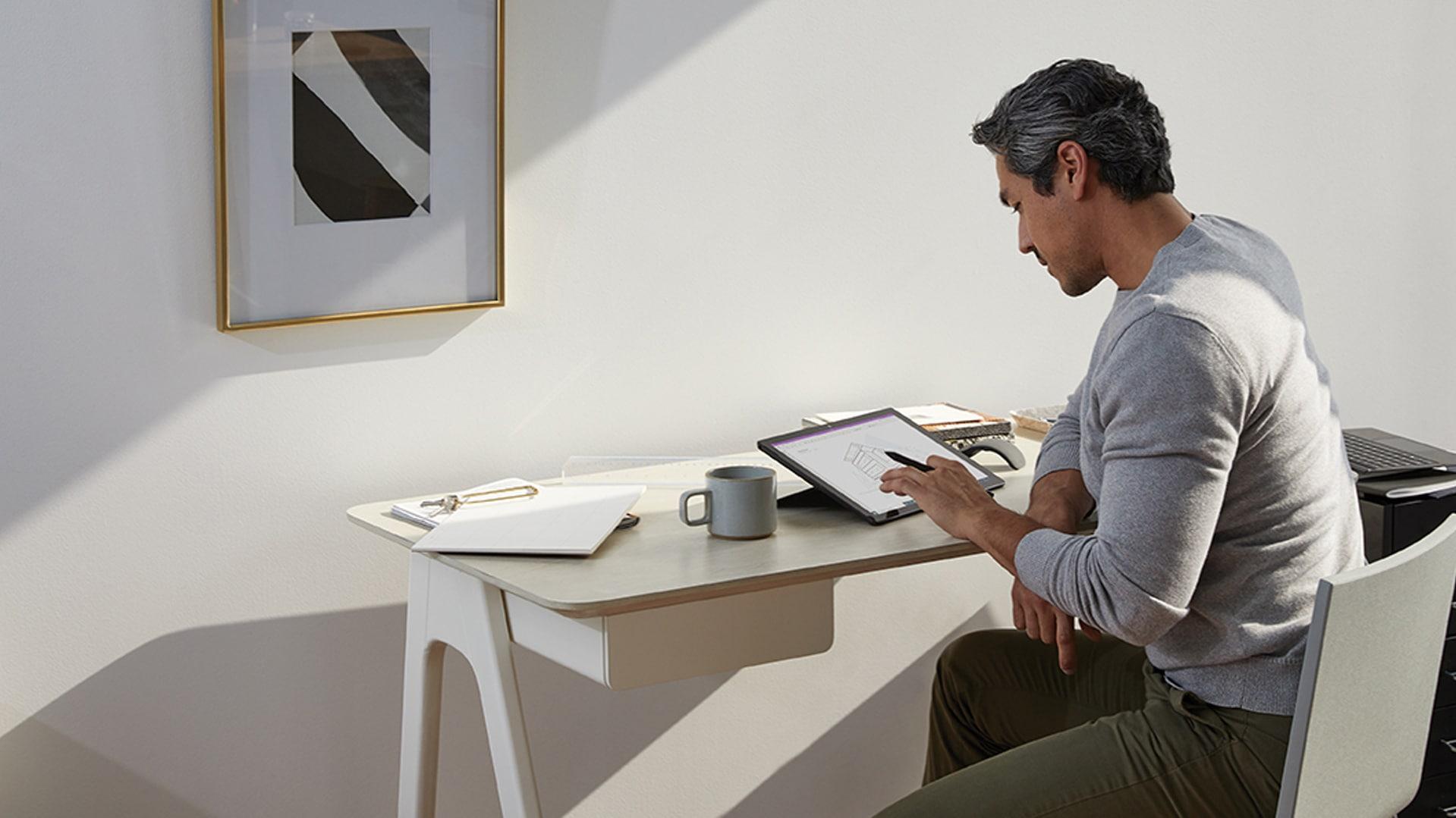 自宅のオフィスで Surface ペンと Surface Pro を使用している男性