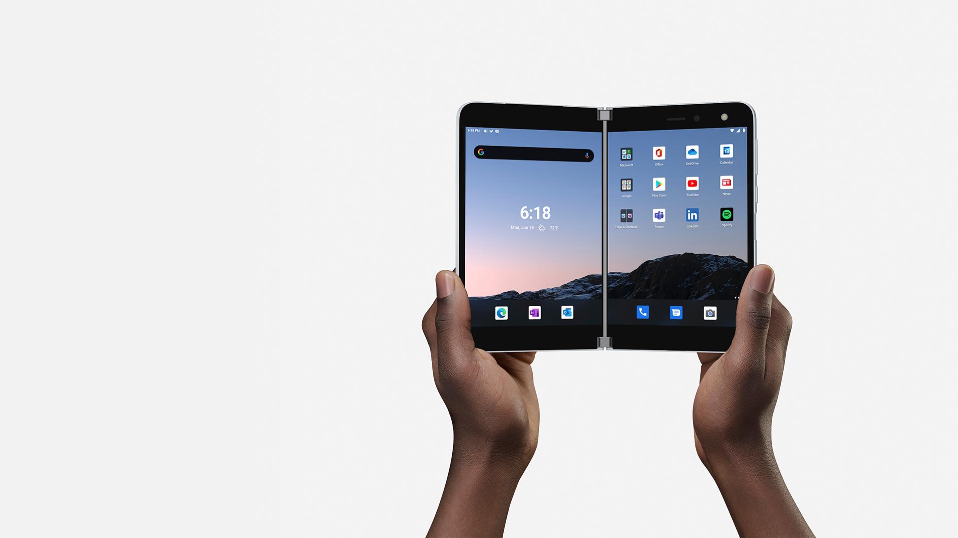 Las manos de una persona sujetan el Surface Duo abierto para mostrar ambas pantallas.