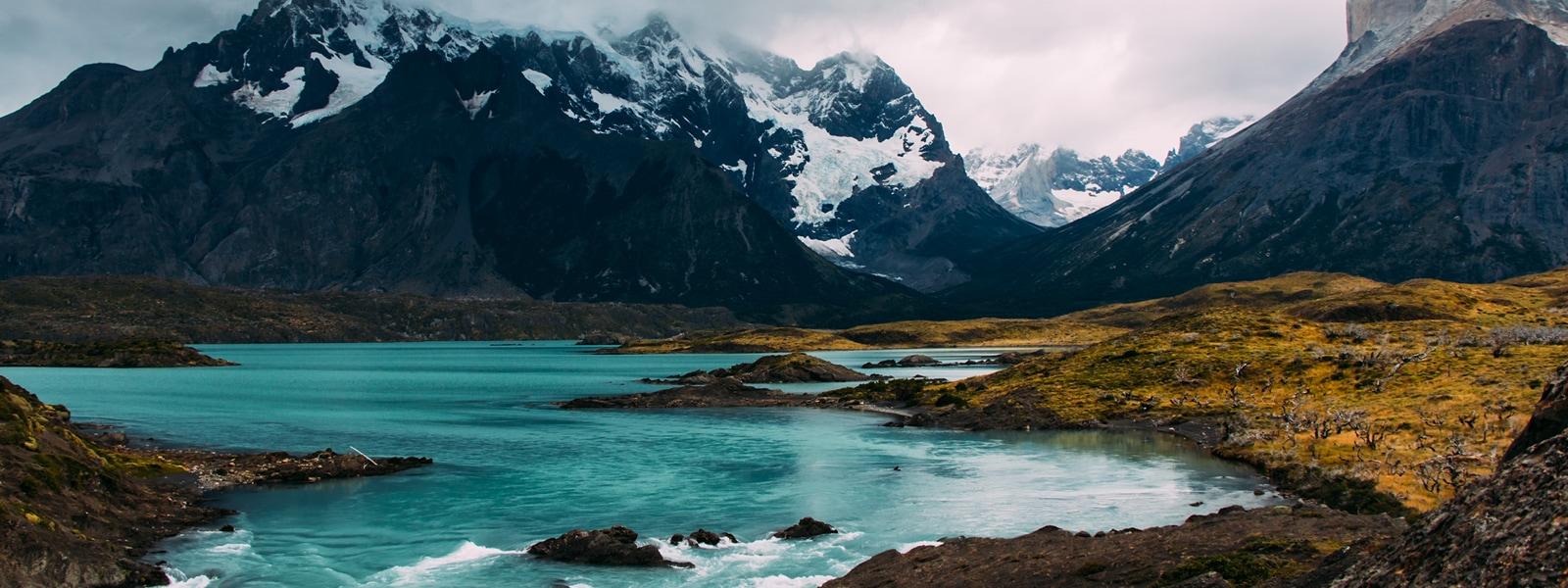 Image of a proglacial river running through snowy mountains