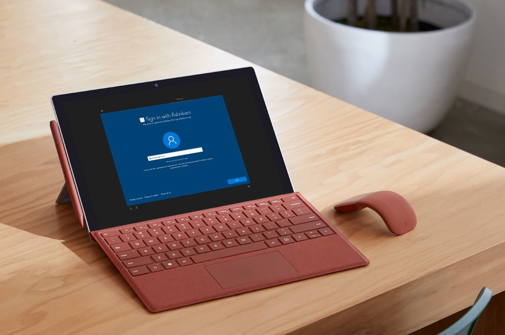 A Surface Pro 7 sits on a table with a Surface Pro Signature Type Cover, Surface Arc Mouse, and Surface Pen in poppy red