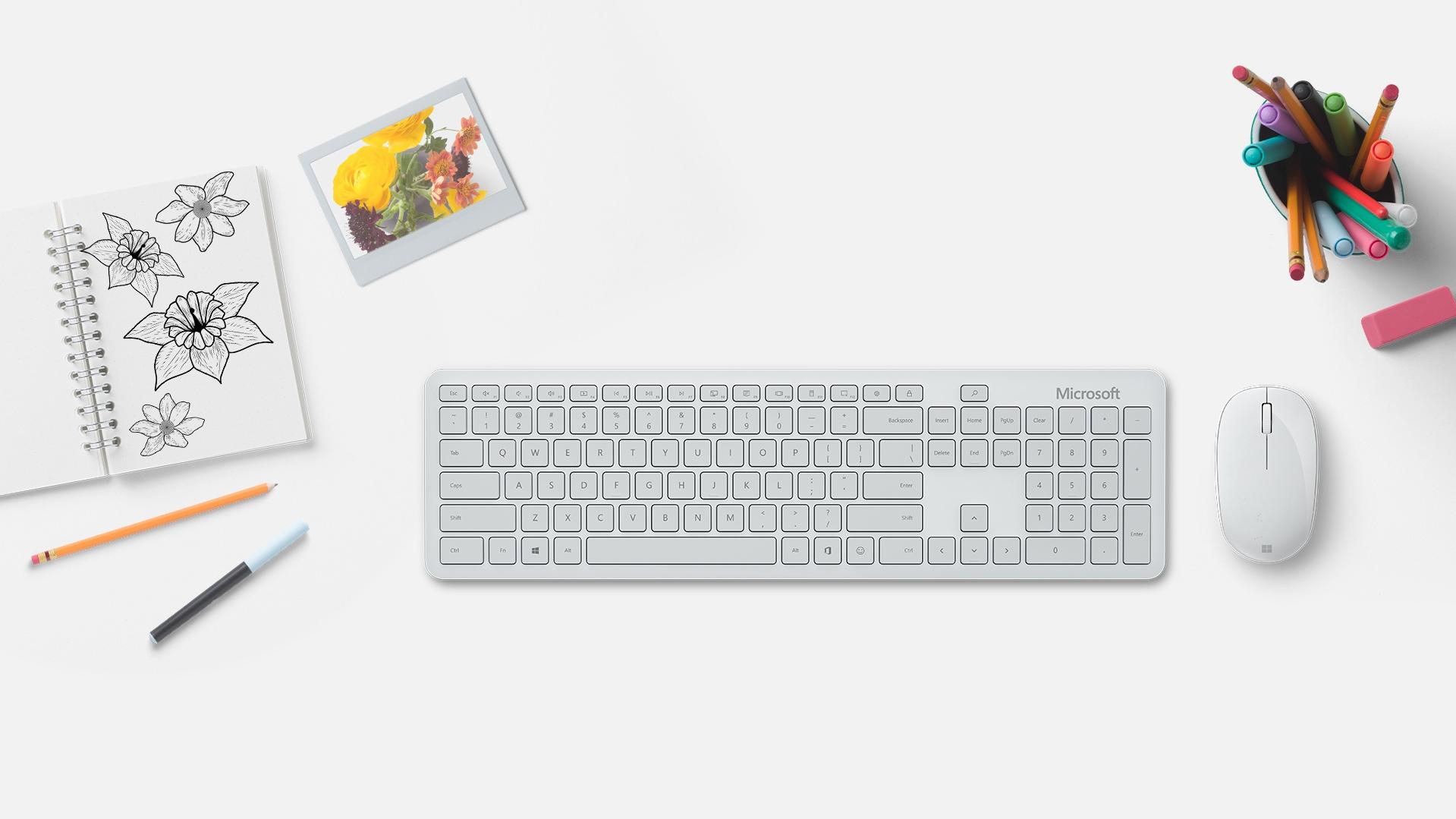 Microsoft Bluetooth-Tastatur neben einer Microsoft Bluetooth-Maus auf einem Schreibtisch mit Stift, Marker, Radierer und Skizzenbuch.