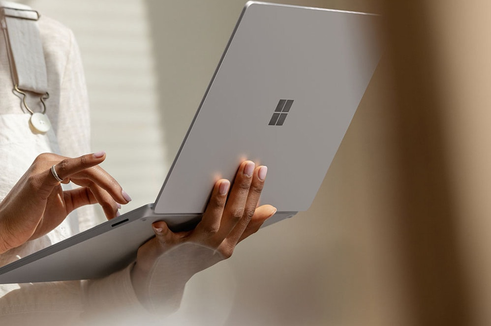 A woman holds her Surface Laptop in her left hand while she types with her right hand