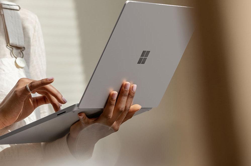 Una mujer sostiene su Surface Laptop en la mano izquierda mientras escribe con la mano derecha