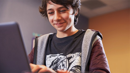 Male middle school student grins while using laptop, seated at desk in bedroom.