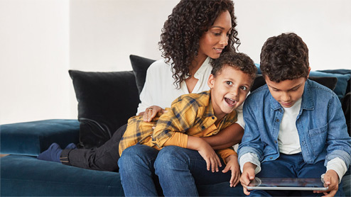 Mother and sons inside home hanging out with child playing games on Surface Go