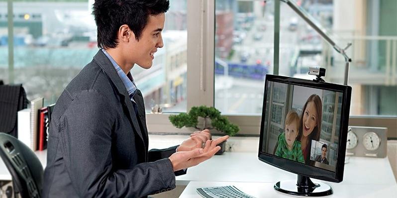 Un hombre sentado en un escritorio frente a un monitor de computadora con una cámara web lifecam studio montada en él