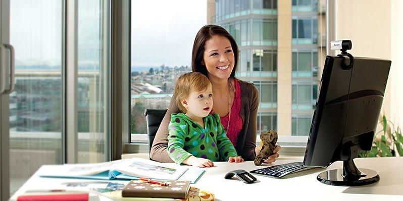 Una mujer con un niño en su regazo, sentada en un escritorio frente a un monitor de computadora con una cámara web lifecam studio montada en ella