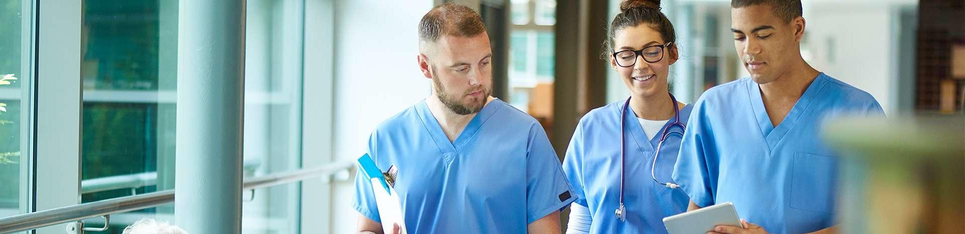 Trois professionnels de la santé marchant dans un bâtiment médical et regardant une tablette.