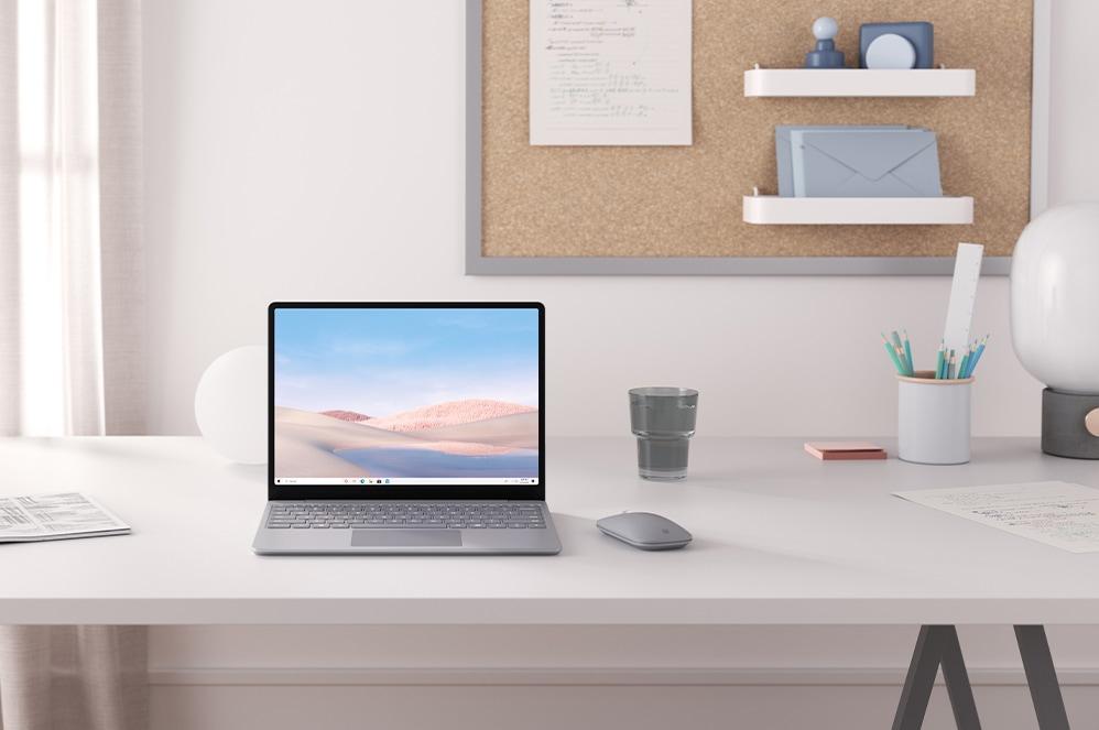 Ein Platin Surface Laptop Go und Surface Mobile Mouse liegen auf einem Schreibtisch.