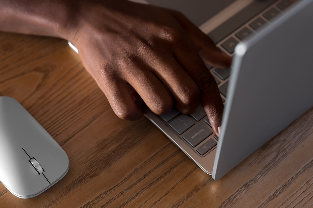 A person's hand typing on the Surface Laptop Go keyboard with a Microsoft Modern Mobile Mouse nearby.