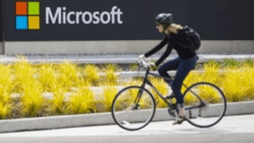 A person riding their bike in front of a Microsoft sign