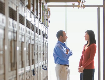 Two people talking in a hallway, standing in front of a wall of servers.