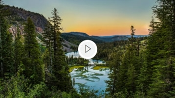 A landscape of a sunset over a forest with a river running through it.