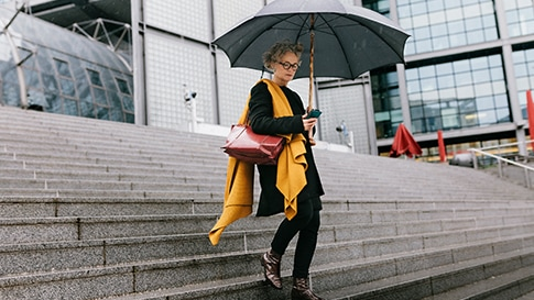 A woman holding an umbrella and checking her smartphone while walking down a set of outdoor stairs
