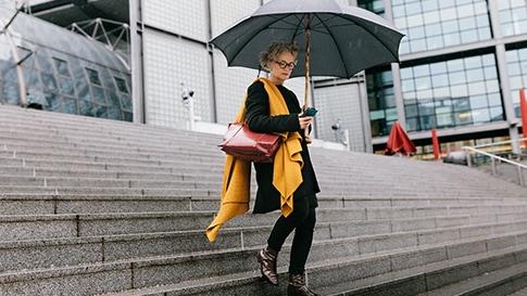 Açık havadaki merdivenlerden elinde şemsiyeyle inerken akıllı telefonuna bakan kadın