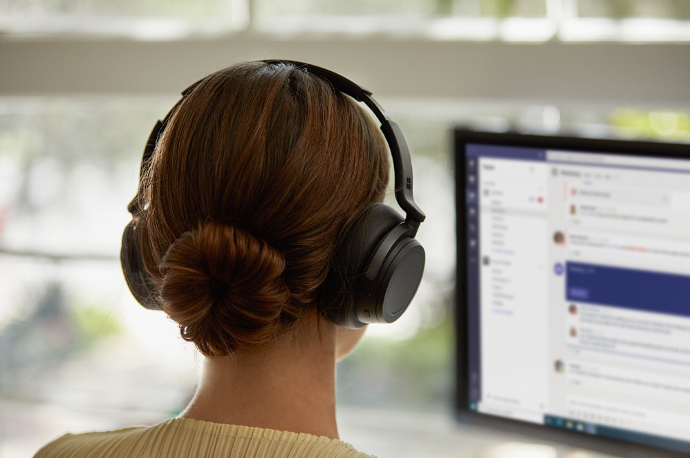 Person wearing Surface Headphones looking at computer screen