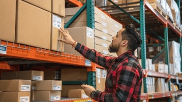 A person working in a warehouse looking at stock